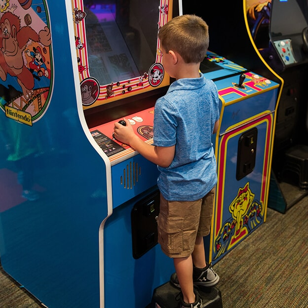 A young patients playing on an arcade machine in our office