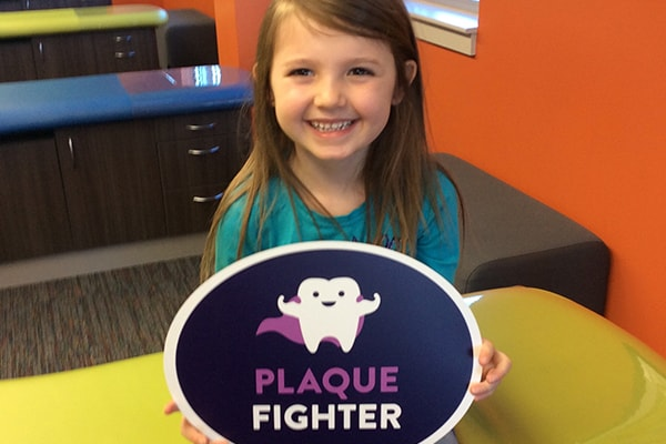 """One of our new patients smiling as she holds up a sign that says """"plaque fighter"""""""