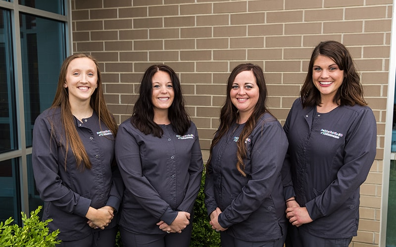 Our four dental hygienists standing in a row and smiling