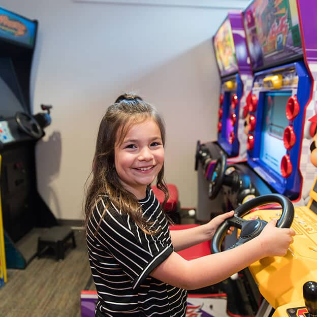 A girl playing on an arcade machine while waiting to receive pediatric dentistry in Terre Haute, IN