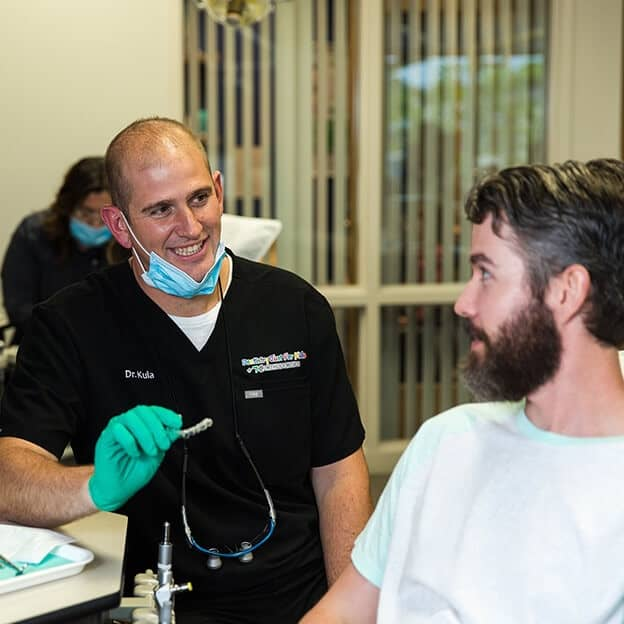 Dr. Kula showing discussing Invisalign® with an older male patient