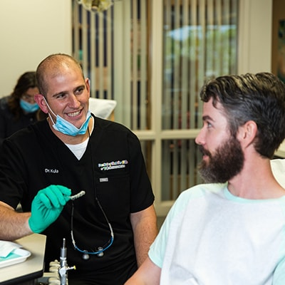 Doctor Kula talking to an adult man about invisalign