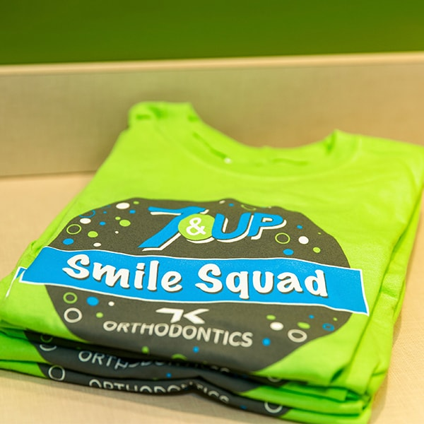 A green shirt with the 7&Up Smile Squad logo on it