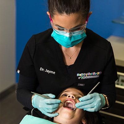Dr. Jayme extracting a tooth from a child