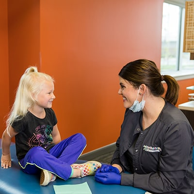 One of our dental hygienists with a little girl smiling