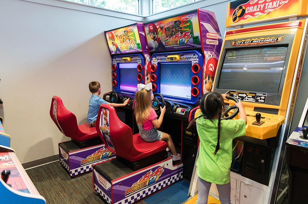 Various children playing on arcade machines