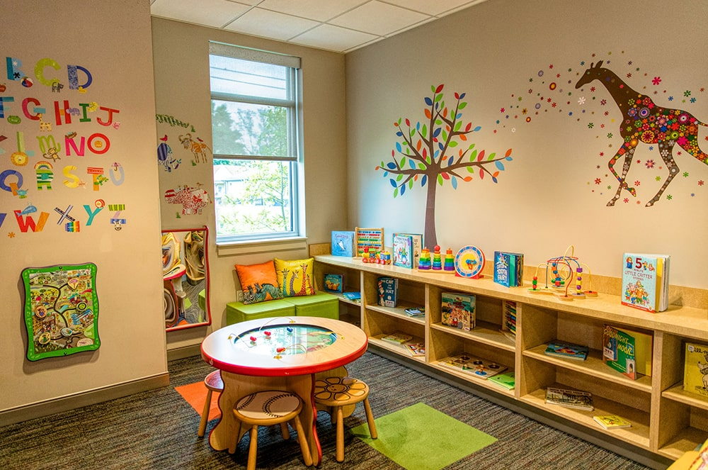 The toddler playroom displaying various colored painting, books, and small tables